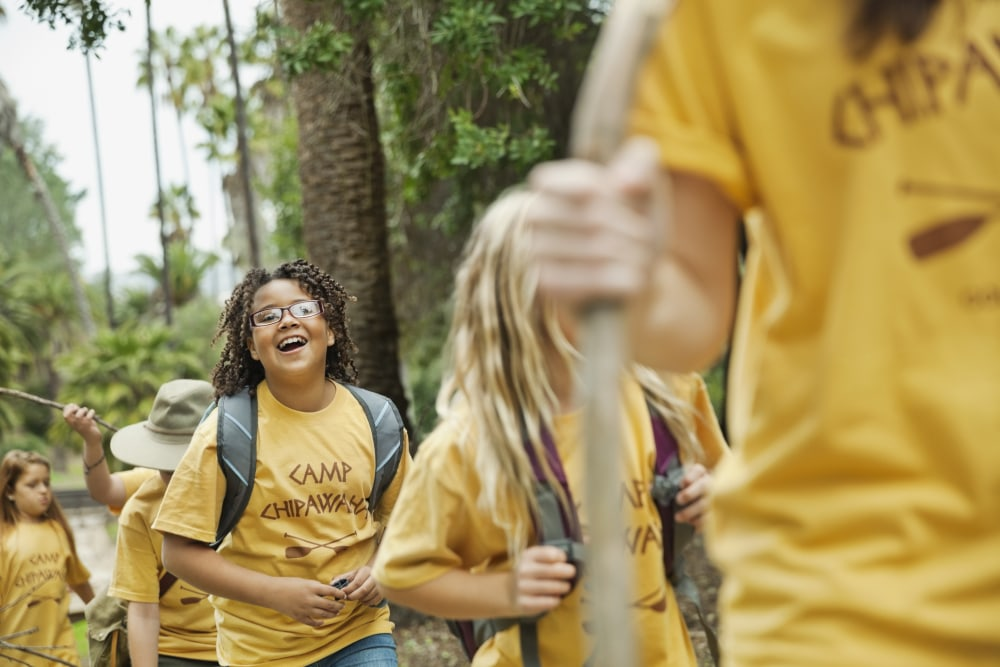 Children at a summer camp hike in the woods in matching camp shirts.