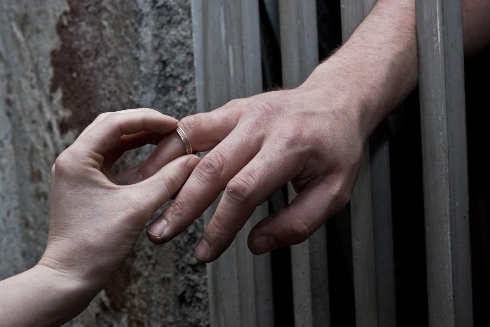 Lover putting wedding ring on prisoner hand