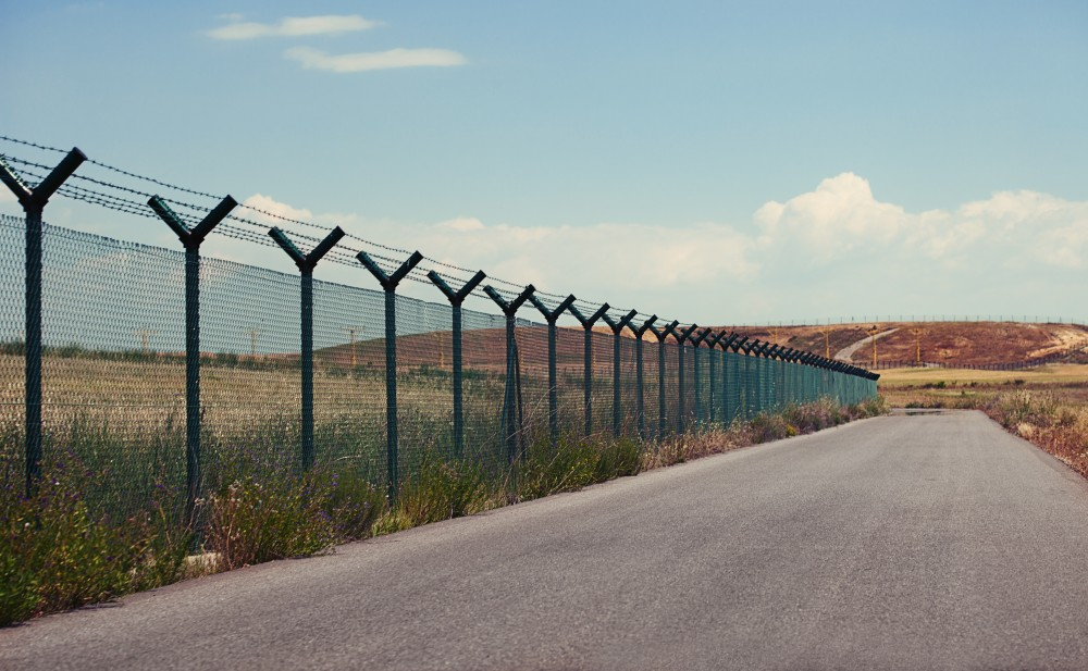 Road next to a fence in a  clear day.