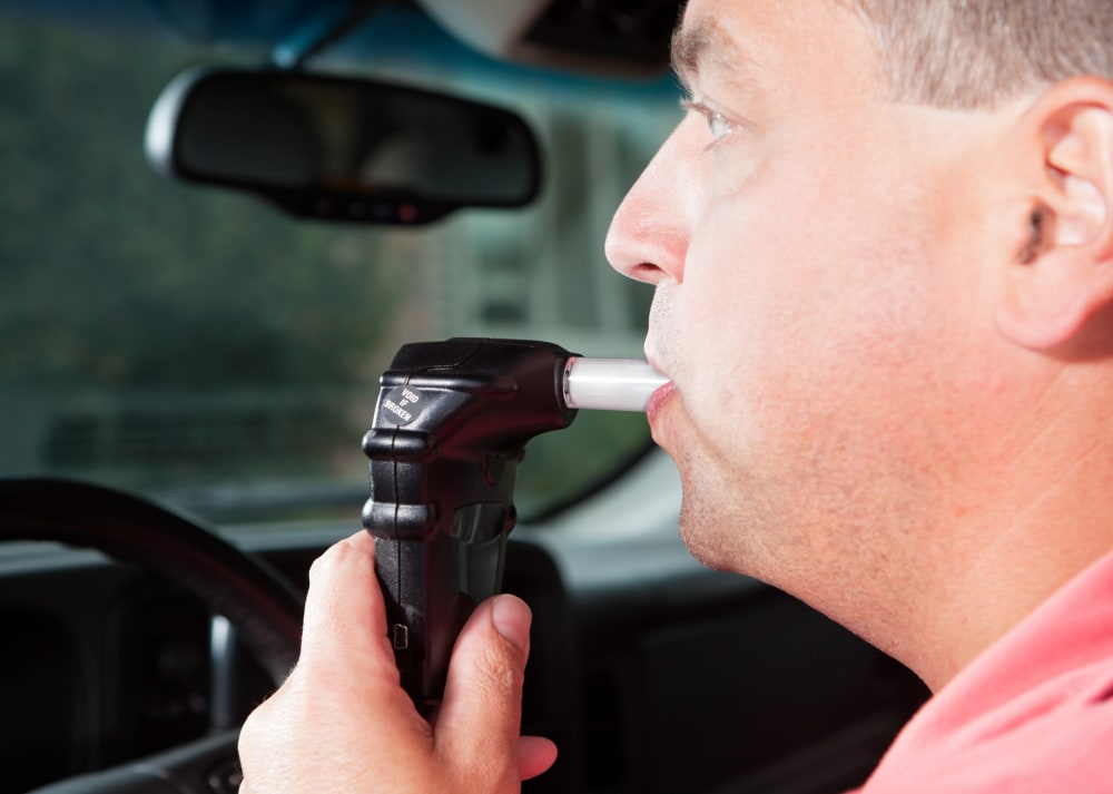 A male driver is blowing into an ignition interlock system which checks his alcohol concentration before allowing the vehicle to be started. Ignition interlock devices may be an alternative sentence for drunk driving or a probation requirement for those who have received a DUI.
