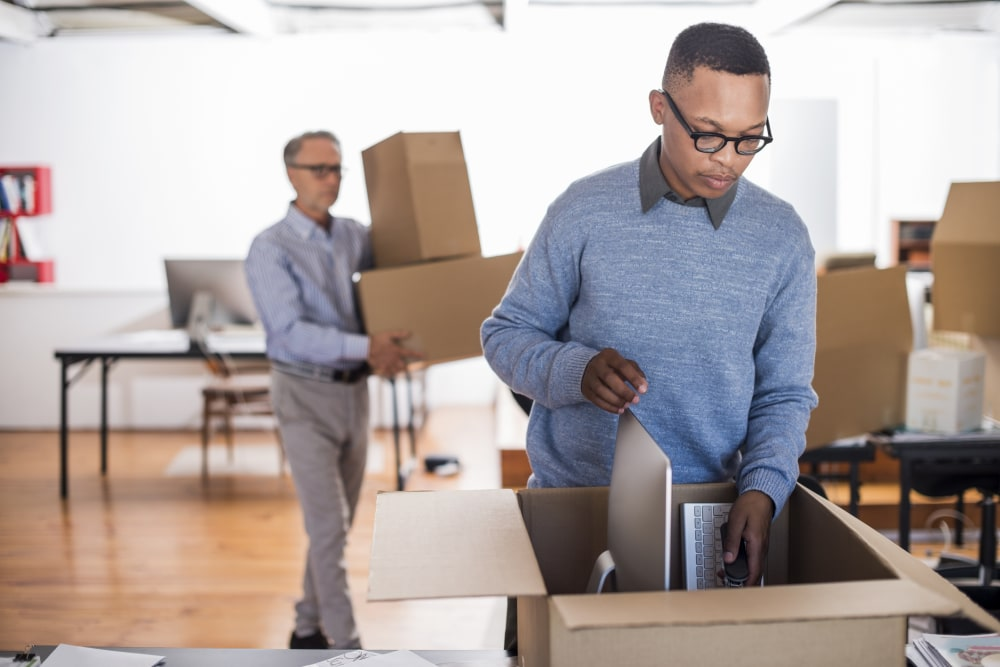 Multi-ethnic businessmen packing cardboard boxes in creative office
