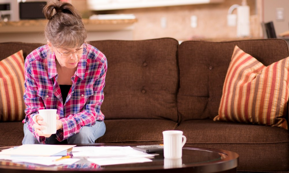 Senior adult woman worries over her past due bills while sitting on home living room sofa.  A pile of invoices on coffee table in front of her.  She is calculating expenses versus budget income.  Frustration among middle-class people.   Great imagery for election season:  home finances, recession, past due bills, mortgage, debt, stress, worry, taxes.