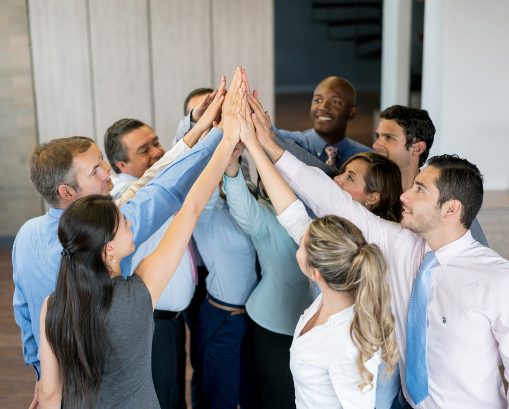 Happy business team celebrating their success at the office with a high five - teamwork concepts