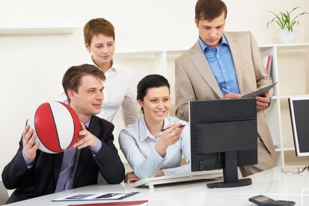 Portrait of business people looking at screen of computer in office