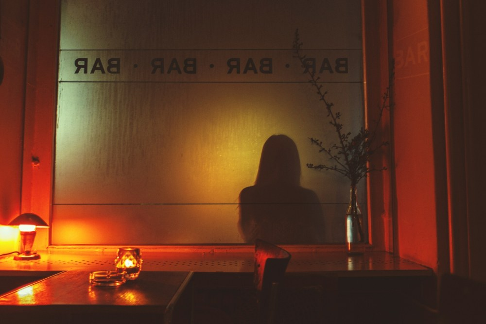 Woman's shadow on the other side of a window in a bar