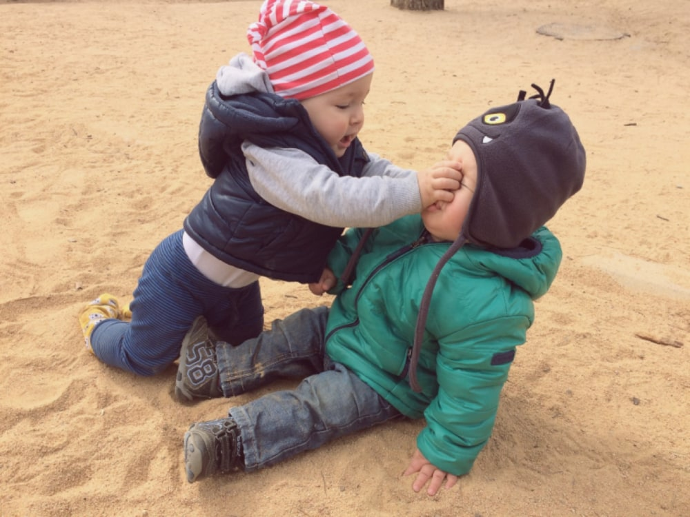 two toddlers fighting on playground sand