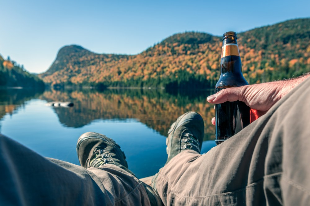 DSLR picture POV of a man relaxing near a lake on a beautiful day of autumn season. There is coloured mountains in background and the lake is calm. The man is holding a beer bottle.