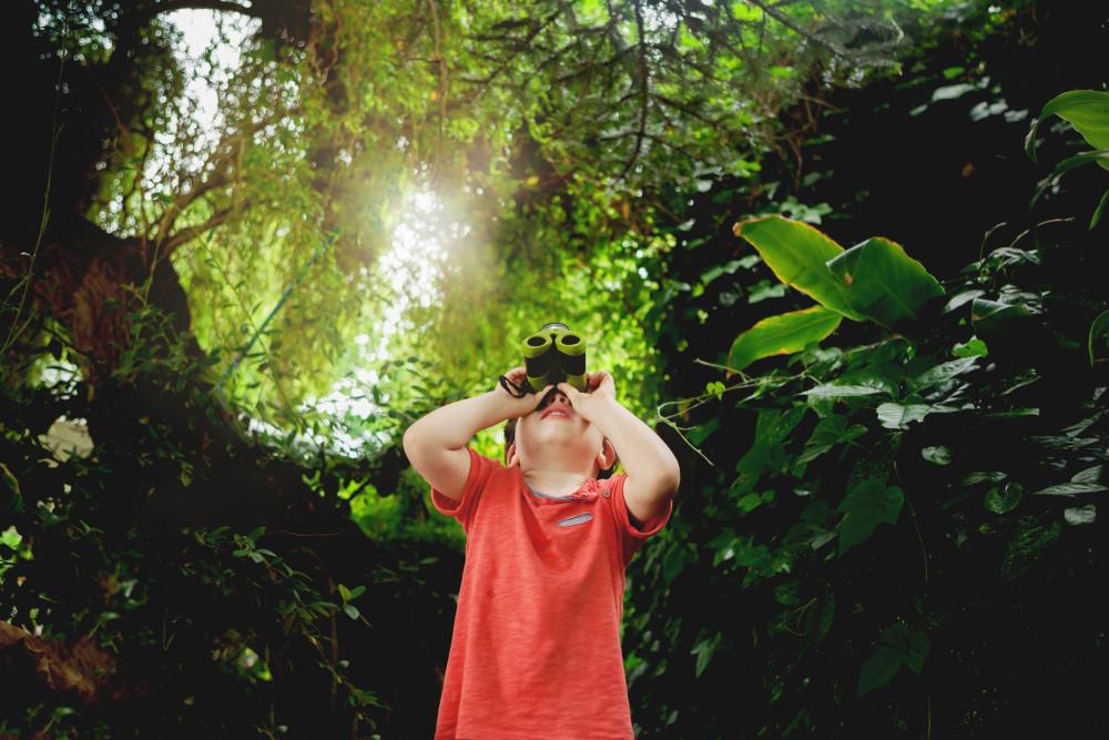 a boy looking in binoculars outdoors