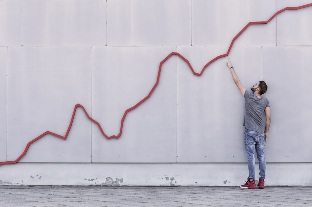 A red bar line graph rises like a financial graph or graphic with a young man pointing at the growth against a wall