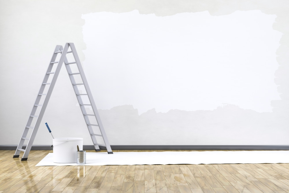 A ladder stands next to a wall that has been half painted with primer