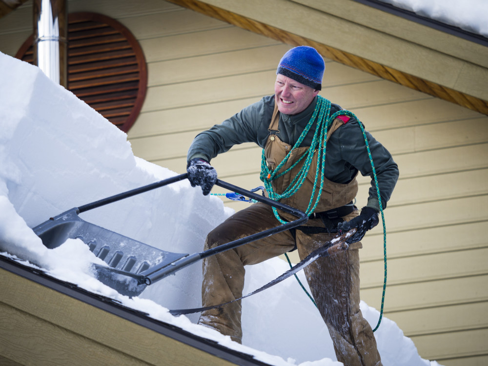 Man busy with clearing snow off of roof with shovel and saw, McCall, Idaho, USA