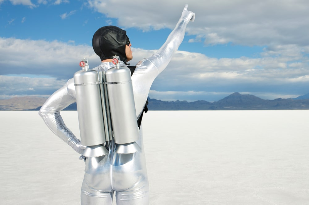 A man in a silver spandex suit with an old pilot's hat and a jetpack on pointing to the sky while standing in the great salt flats
