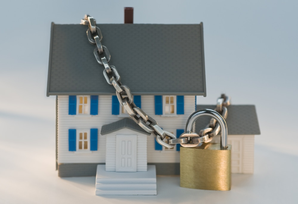 A miniature home with a chain and lock across it