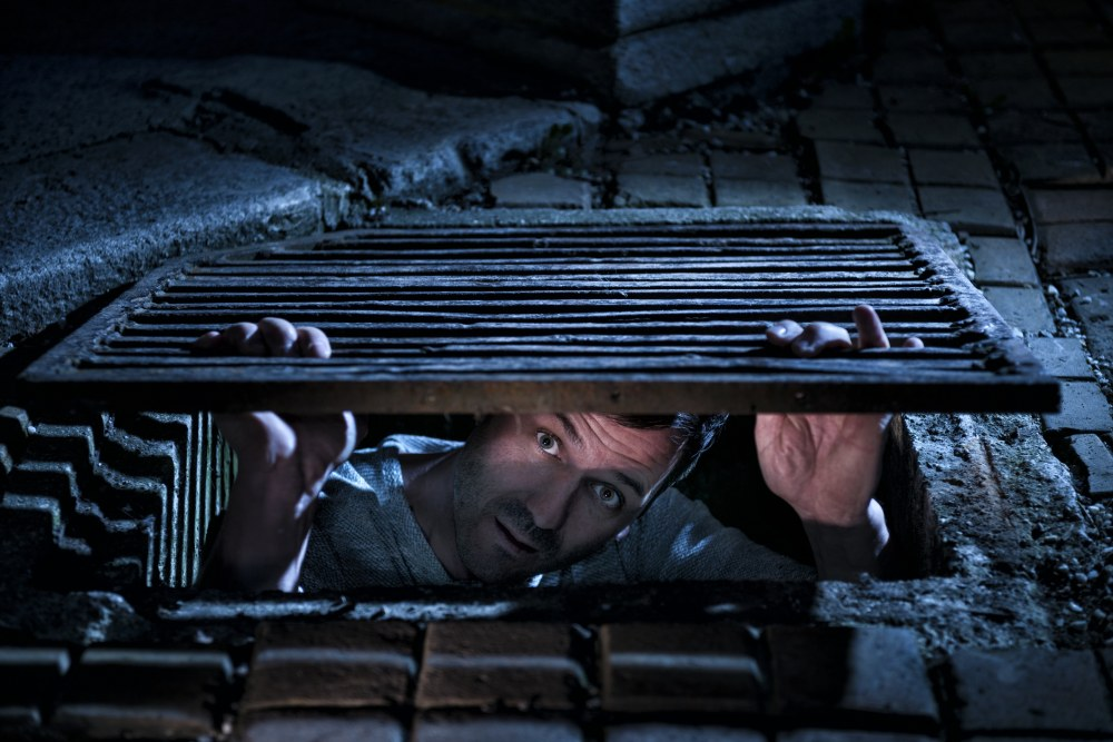 Man looking scared out of a manhole at night