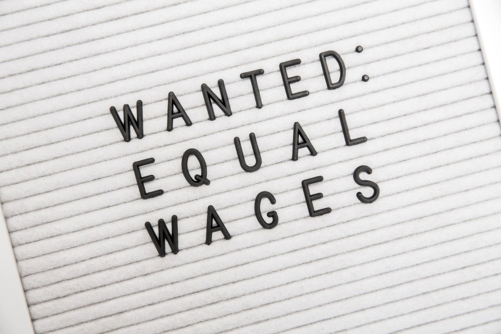 """A phrase on a letterboard that says """"Wanted: Equal Wages."""" This phrase depicts the need for equality, equal pay, and the end of job discrimination and sexism."""
