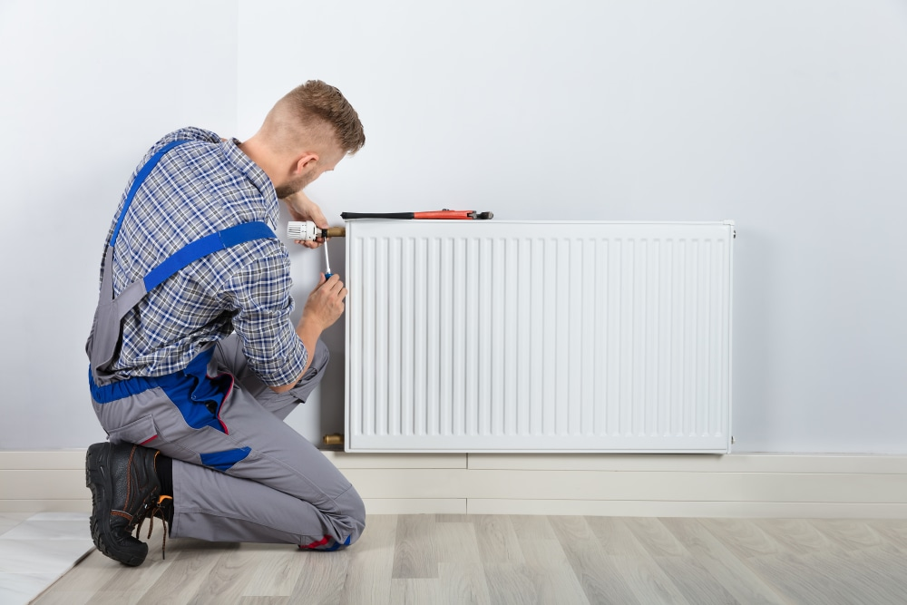 Plumber Fixing Thermostat With Screwdriver And Wrench On Radiator