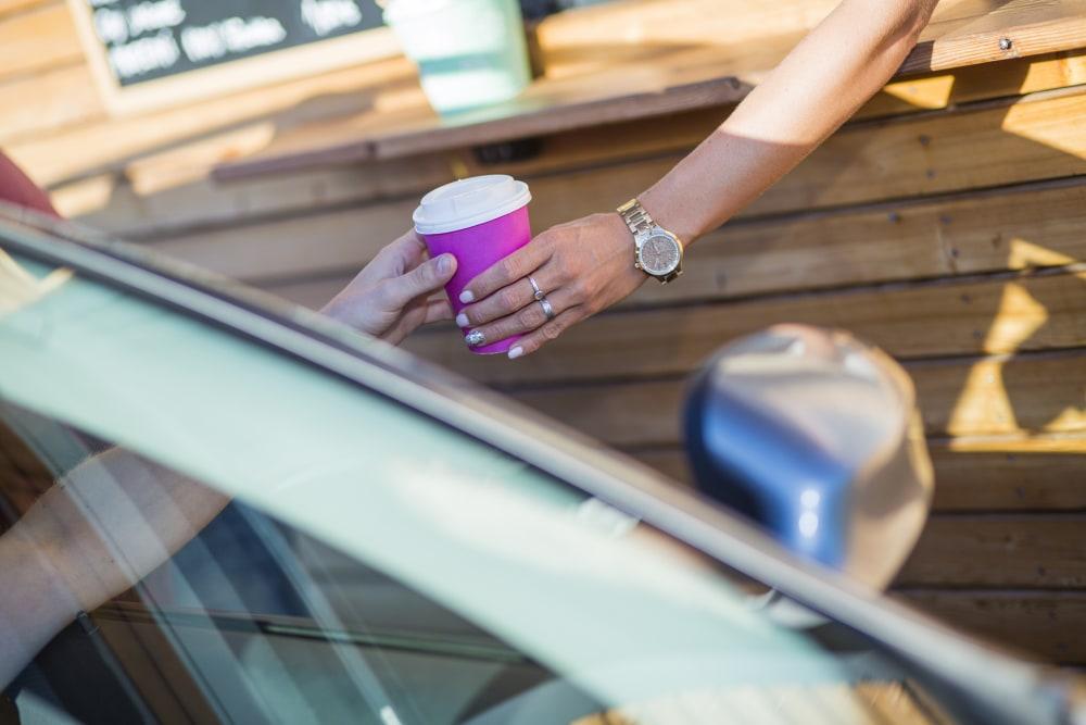Cashier in a drive through coffee shop serving take away coffe.