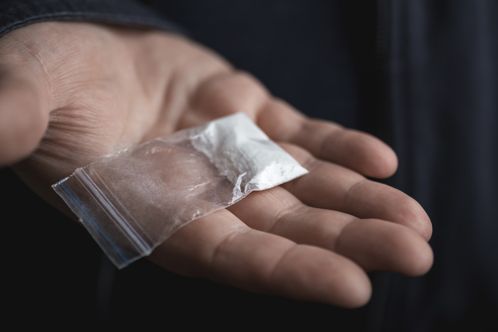 Hand holding on palm plastic packet with cocaine powder or other drugs