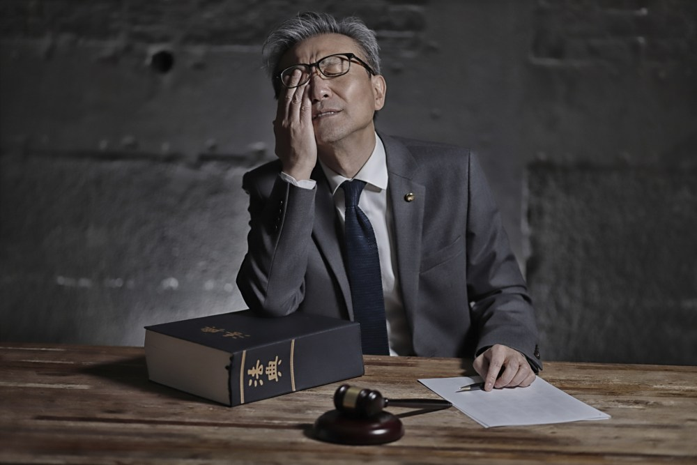 Man in a suit rubs his eyes at a desk covered in papers and a legal book.