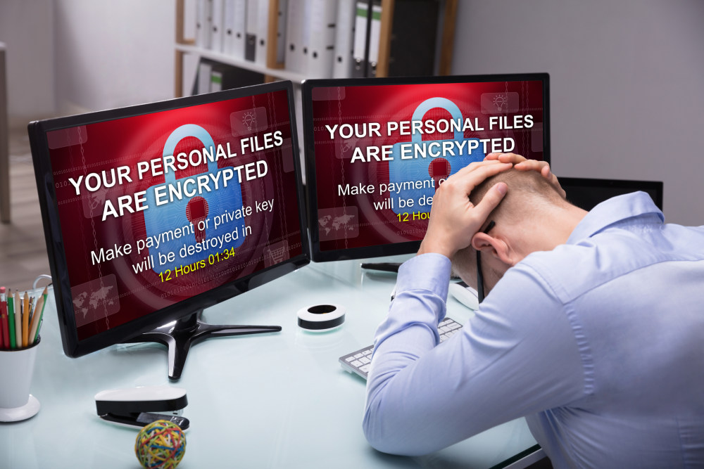 Stressed Businessman Sitting In Office With Computer Screen Showing Personal Files Encrypted Text