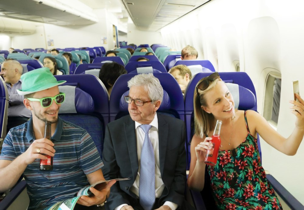 A man in a suit looking annoyed trapped between two airplane passengers drinking and carrying on