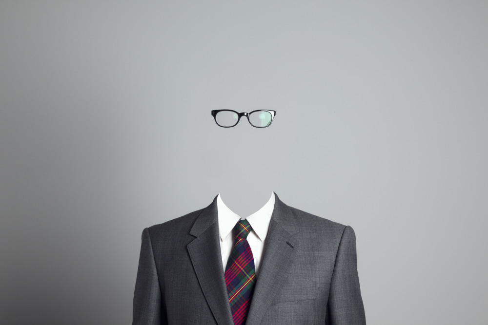 A head and shoulders shot of a business person wearing glasses, but their face is invisible.