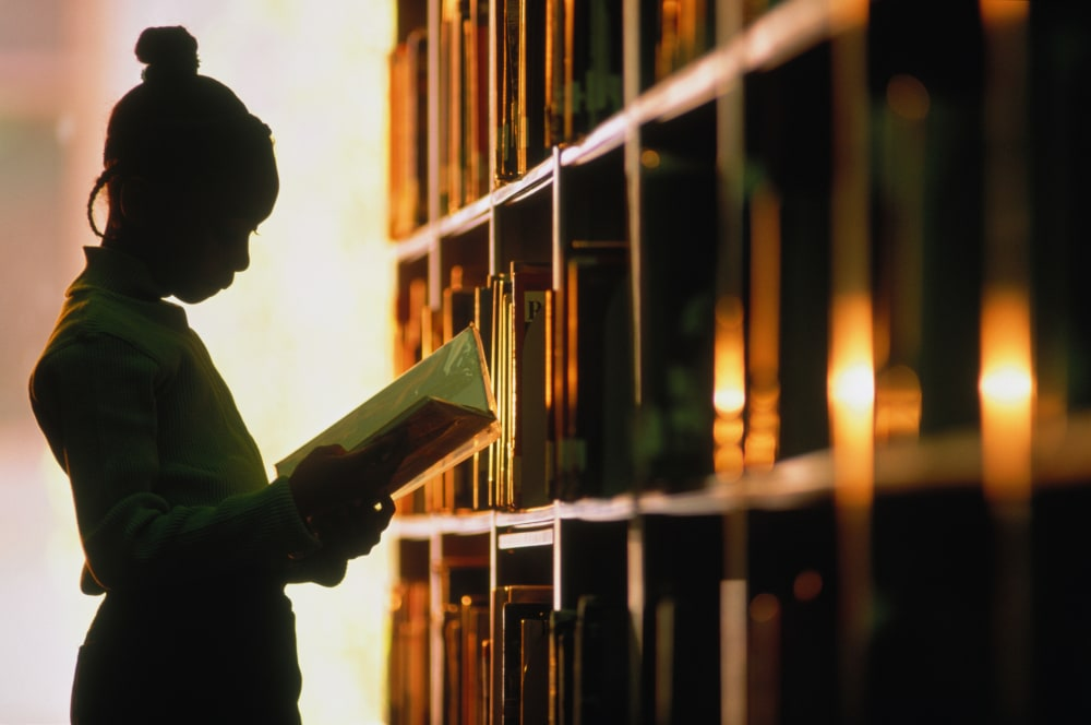 Young girl in silhouette, reading in a library