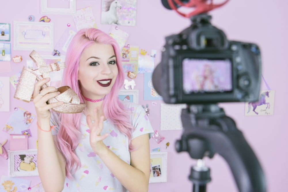 Pink-haired woman holding up a shoe in front of a camera.