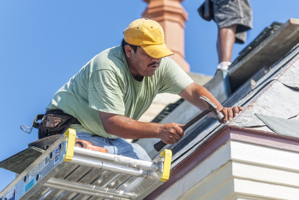 Roofer putting shingles on a house
