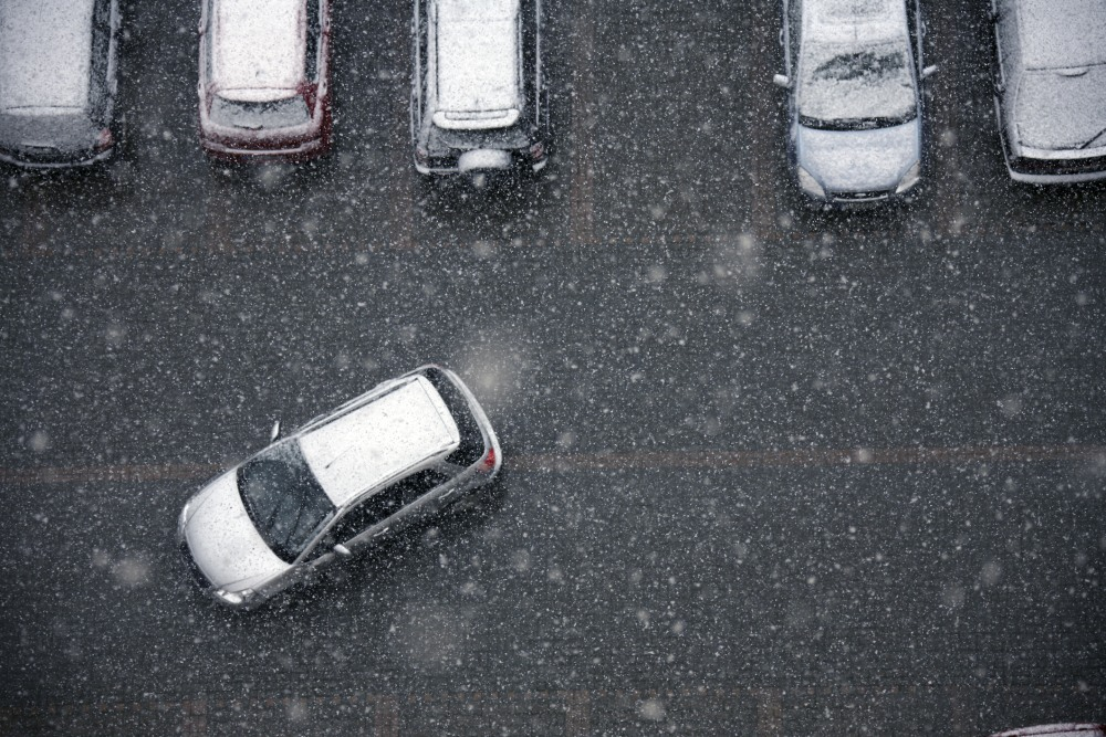 elevated view of parking lot during snow.