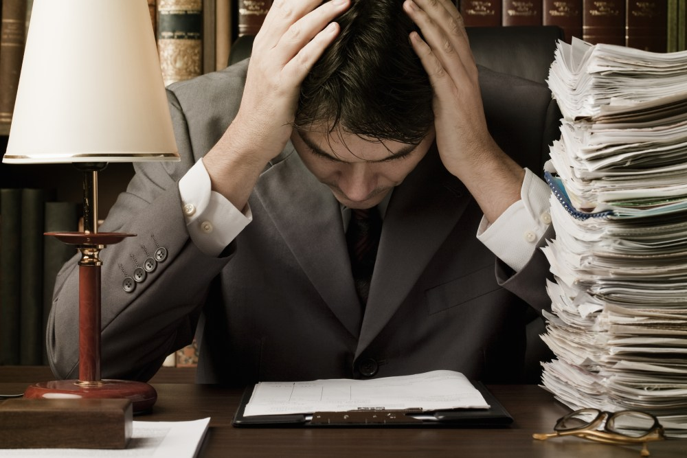 Man with hand on his head and surrounded by paperwork