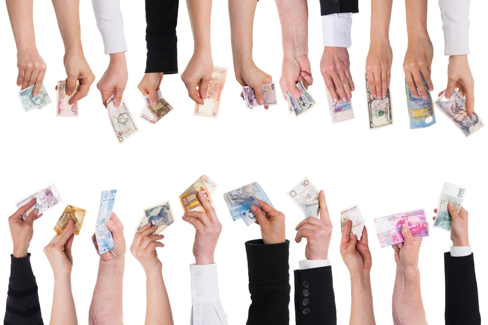 Hands holding various currency denominations.