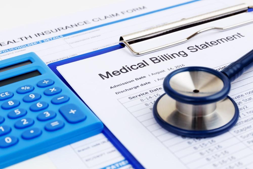 Calculator, medical billing statement, stethoscope