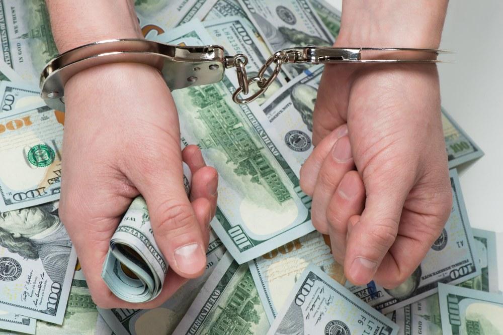Hands in handcuffs hold money