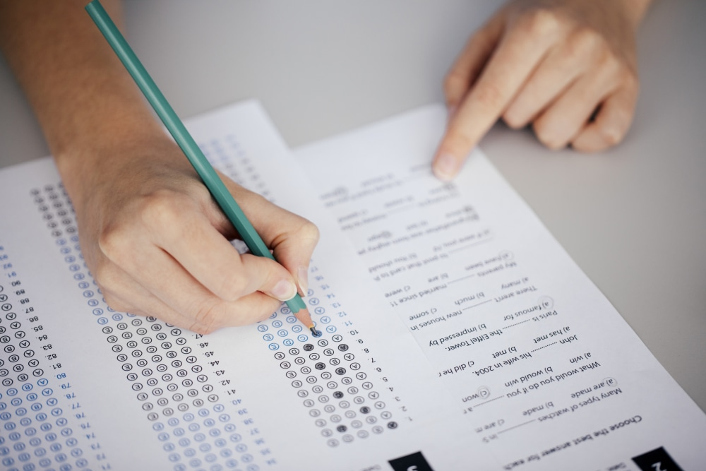 Close up of hands of student doing test.