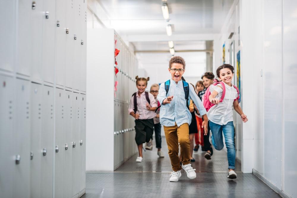 cute funny pupils running through school corridor
