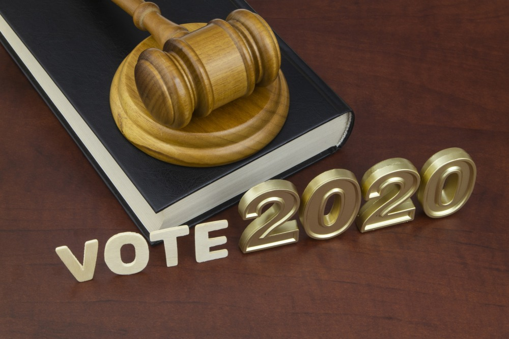 Wooden judge gavel, legal book, letters vote and numbers 2020. Concept of election in year 2020.
