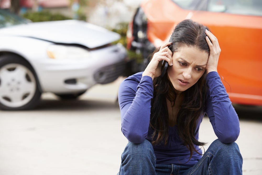 Female Driver Making Phone Call After Traffic Accident With Head In Hands.