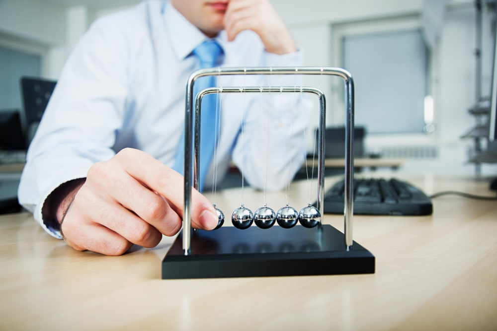 Worker playing with Newton's cradle in office
