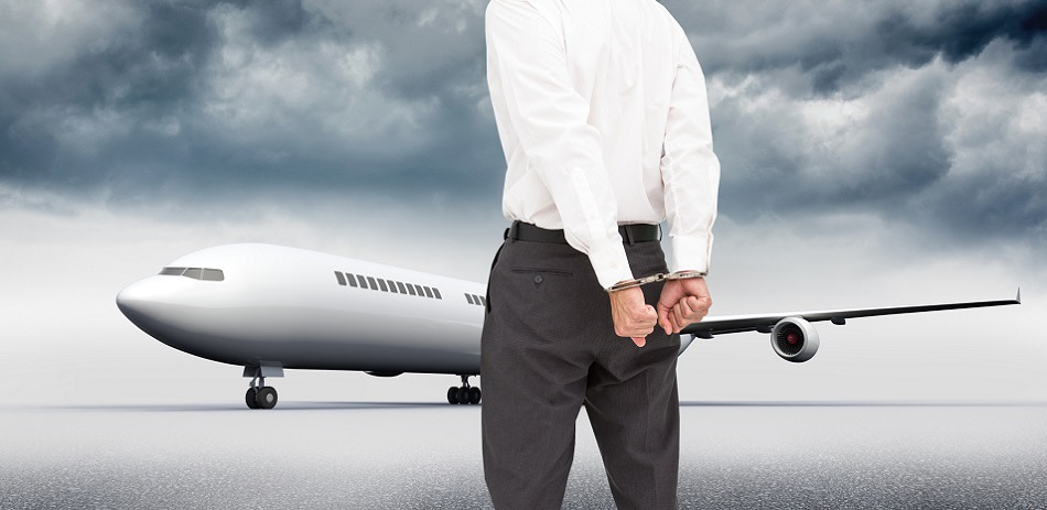 a man (from the neck down) in handcuffs in front of an airplane