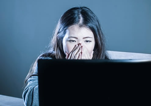 young worried Asian Korean student girl looking depressed and desperate studying with laptop computer in stress for exam feeling frustrated stalked and harassed on internet bullying