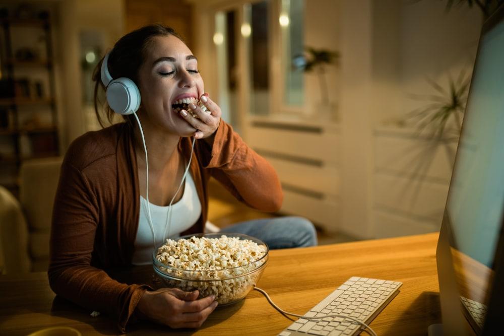 Woman watching t.v. at home eating popcorn.
