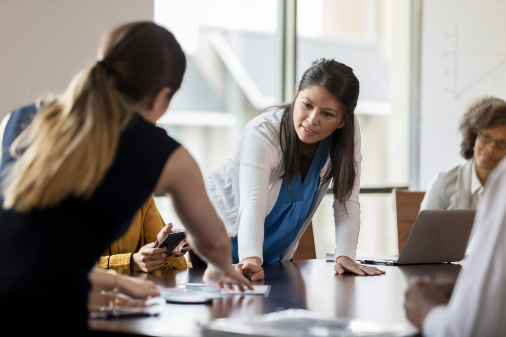 Mid adult Asian businesswoman discusses a chart or document with a female colleague during meeting.