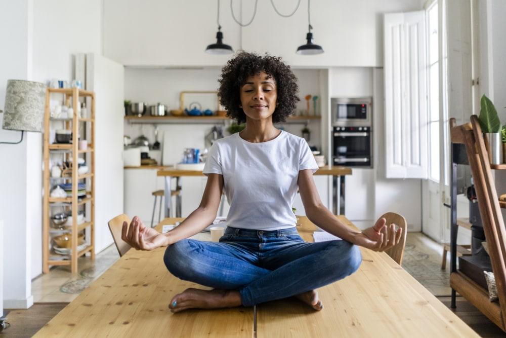 Woman sitting cross-leged on a table meditating
