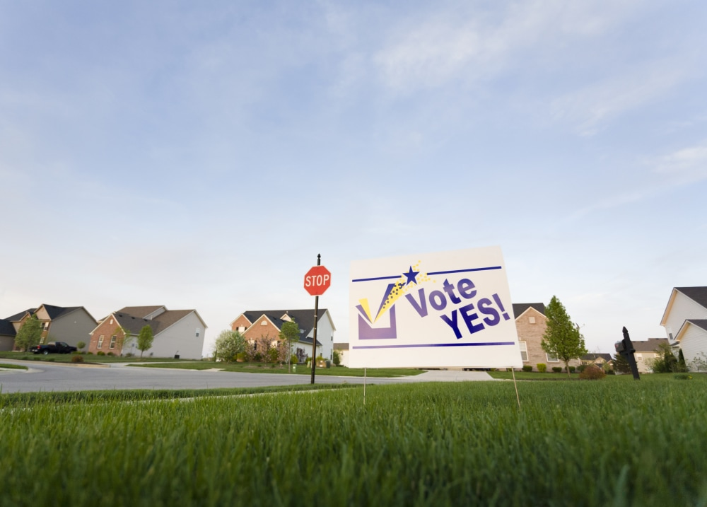 Image of a lawn sign in a neighborhood reading Vote Yes