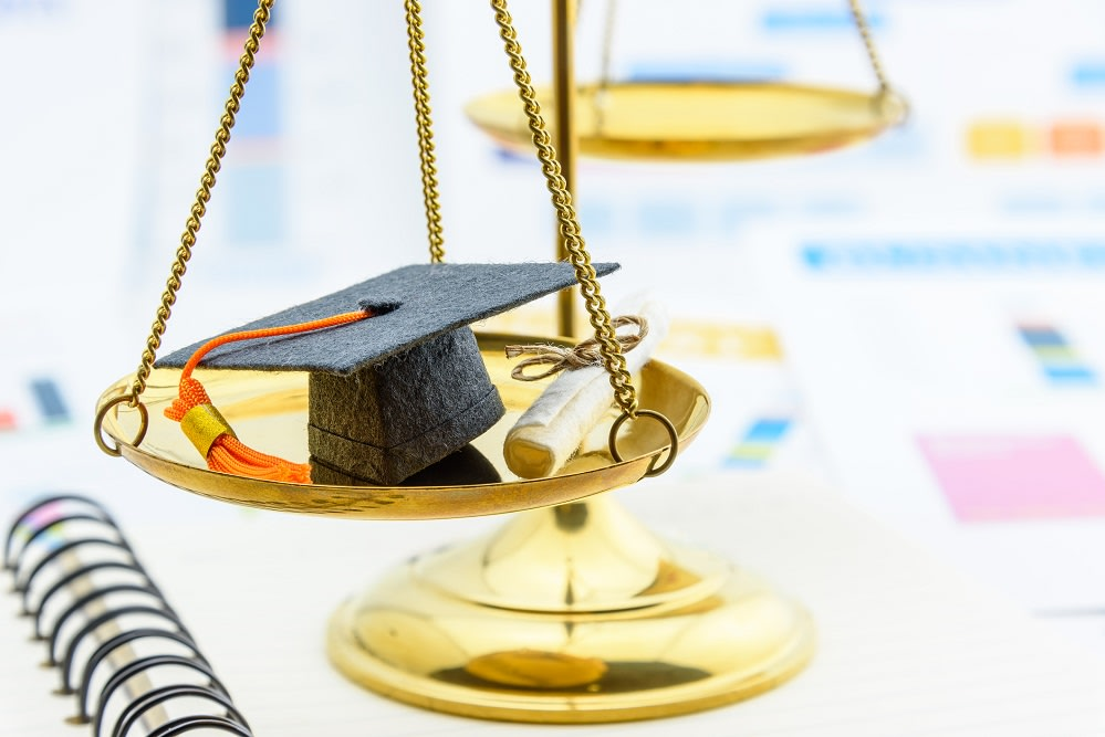 Graduate study abroad program concept : Graduation cap on a balance scale of justice and a certificate / diploma. Graduate study abroad program is a program that accept students from foreign countries