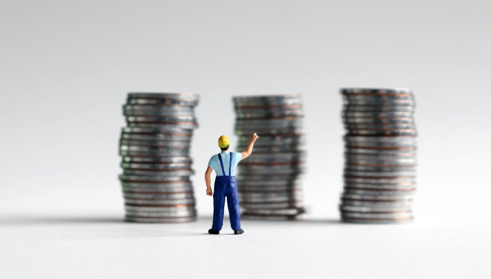 A miniature man pointing at three piles of coins.