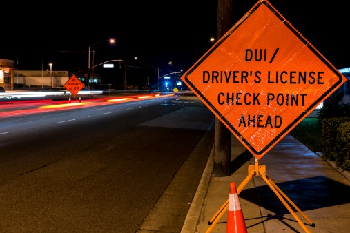 Road at night with sign announcing that a DUI checkpoint is ahead.