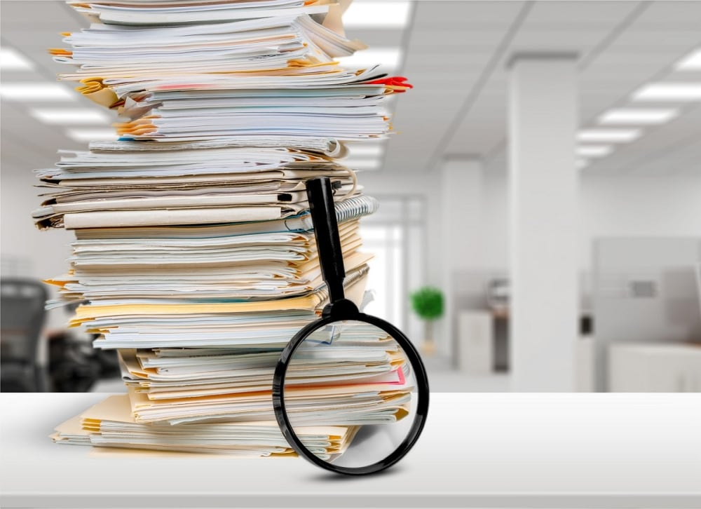 Stack of documents and magnifying glass on office table