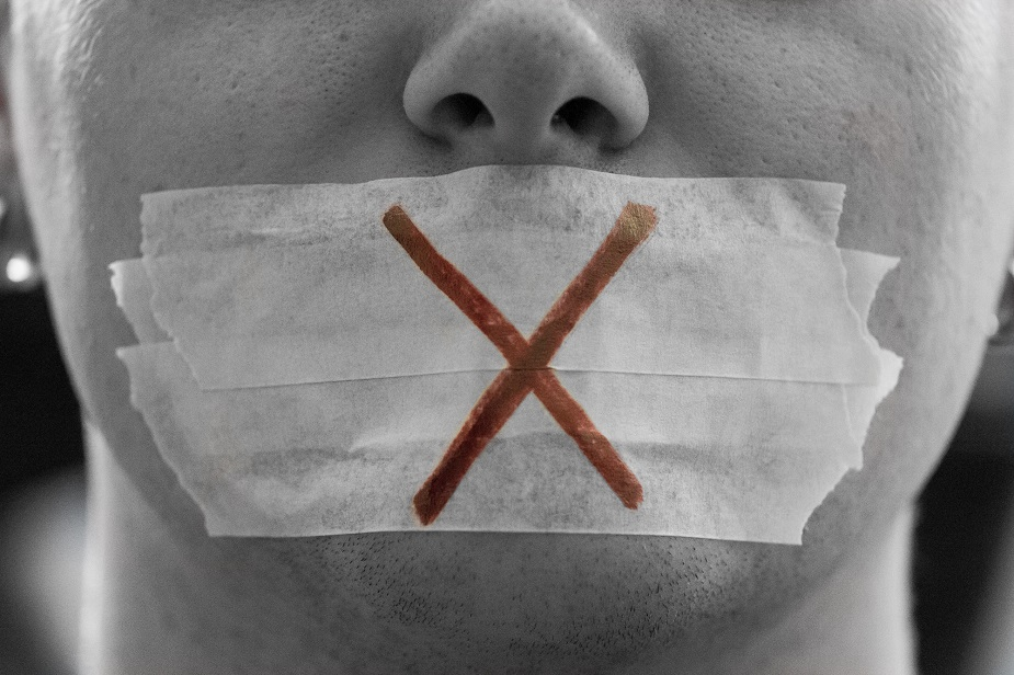 """""""A male face with a taped mouth and a red cross on it symbolizing censorship.Censorship is all around.Freedom of speech is the political right to communicate one's opinions and ideas via speech. The term freedom of expression is sometimes used synonymously, but includes any act of seeking, receiving and imparting information or ideas, regardless of the medium used. In practice, the right to freedom of speech is not absolute in any country and the right is commonly subject to limitations, as with libel, slander, obscenity, copyright violation and incitement to commit a crime."""""""
